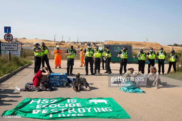Environmental activists from HS2 Rebellion sit locked together in the road to block a gate providing access to a site for the Chiltern Tunnel on the...