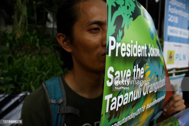 Environmental activists from Living Environmental Facility a nongovernmental organizations that focus on the environment wears an orangutan mask held...