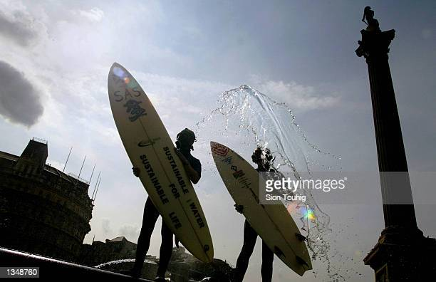 Environmental activists from Surfers Against Sewage wear gasmasks and carry surfboards during a protest in Trafalgar Square August 22 2002 in London...