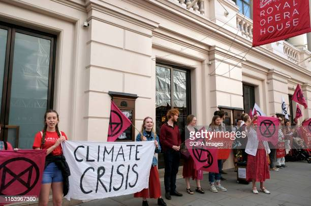 Environmental Activists hold a banner and flags outside the Royal Opera House during a protest Environmental Activists from Extinction Rebellion...