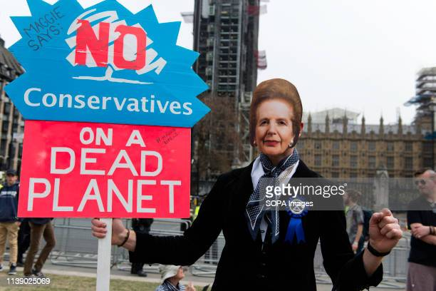 Environmental activists is seen holding a placard saying Maggie says No Conservatives on a dead planet during the Extinction Rebellion march...