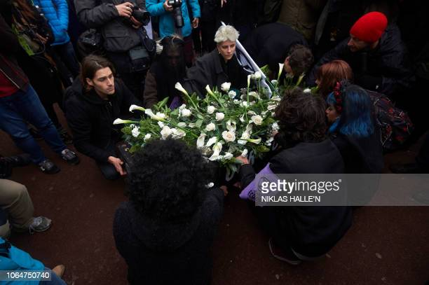 Environmental activists lay a coffin with our future written on it outside the gates of Buckingham Palace in central London on November 24 during a...