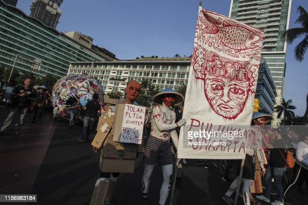 Environmental activists march to protest singleuse plastics alongside 4metertall Anglerfish plastic monsters made from various plastic wastes along...