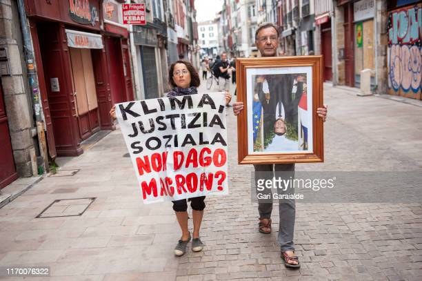 Environmental activists of the Basque movement Bizi walk the streets of Petit Bayonne with photographs of Emmanuel Macron, that were stolen from...