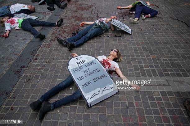Environmental activists participate in a die-in during a rally for action against climate change in the Financial District October 7, 2019 in New...