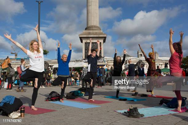 Environmental activists practice yoga while protesting about Climate Change during an occupation of Trafalgar Square in central London the third day...