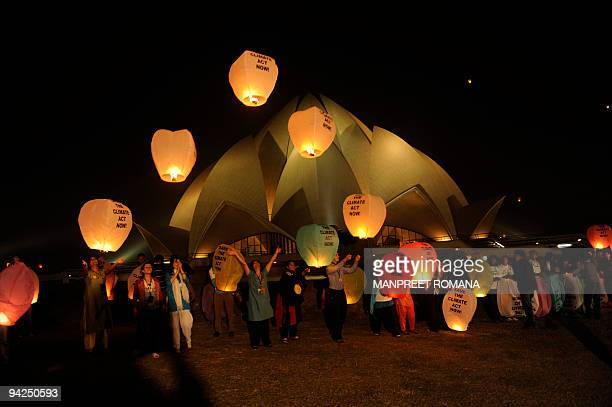Environmental activists release lanterns into the sky against the backdrop of the Lotus Temple in New Delhi on December 10 International NGOs...