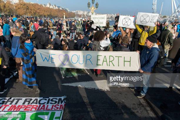 Environmental activists seen holding a banner on Westminster Bridge Extinction Rebellion activists gathered at five main bridges in London to raise...