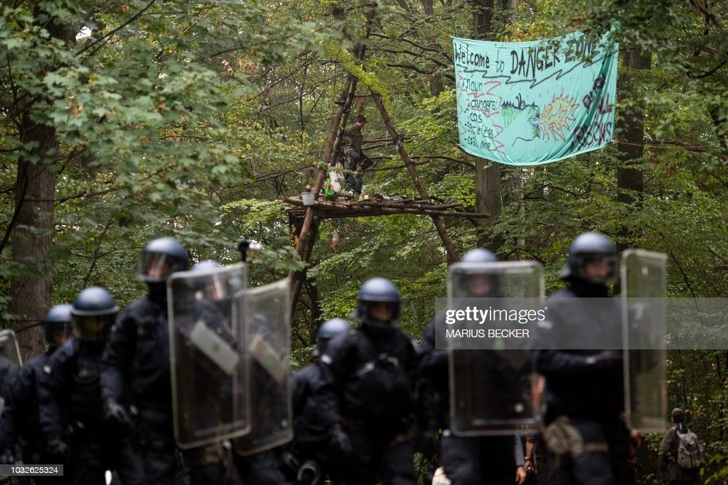 Environmental activists sit in a so-called Tripod tree house as riot police arrive to clear the Hambacher Forst forest in Kerpen, western Germany, on September 13, 2018. - German activists living in treehouses to protect the ancient forest from being razed for a nearby coal mine were bracing for a forced eviction by police, in a major escalation of the long running environmental battle. (Photo by Marius Becker / dpa / AFP) / Germany OUT