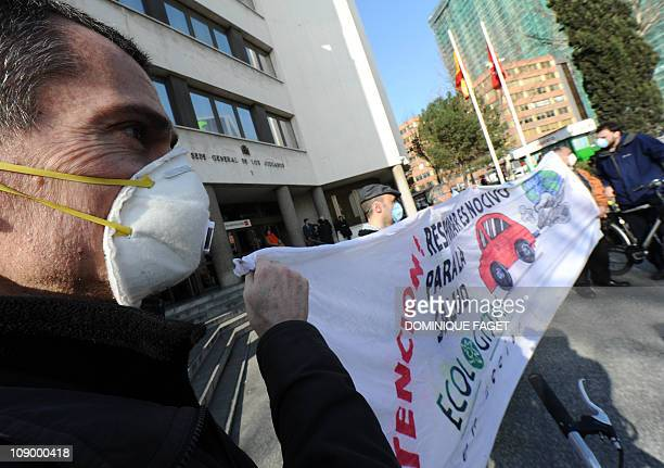 Environmental activists stand behind a banner as thye demonstrate on February 11 2011 in Madrid to demand emergency measures to clear a thick layer...
