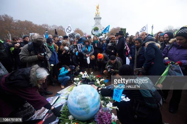 Environmental activists surround a coffin with our future written on it layed at the gates of Buckingham Palace in central London on November 24...