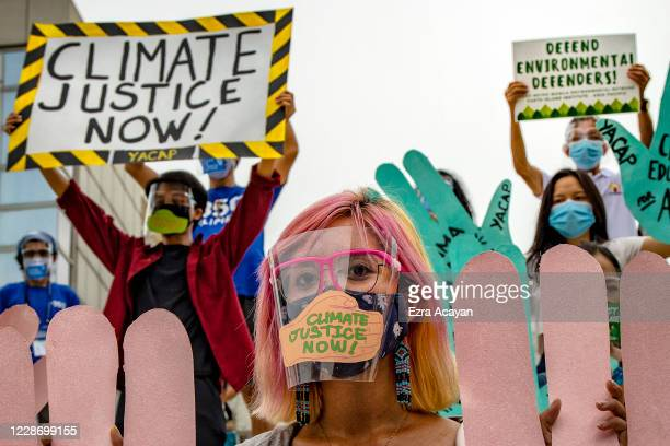 Environmental activists, wearing facemasks and face shields to protect against COVID-19, take part in a rally coinciding with global protests on the...