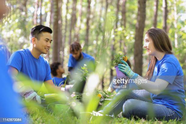 environmental beautification. volunteers plant flowers, plants at local park in spring. - giornata mondiale della terra foto e immagini stock