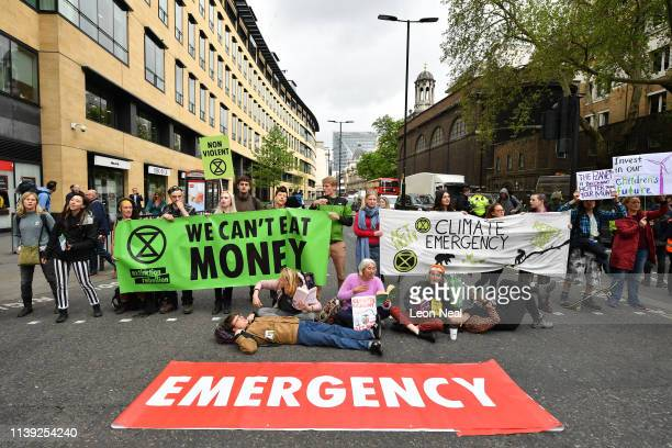 Environmental campaigners from the Extinction Rebellion group block a junction at London Wall by Deutsche bank as part of their ongoing actions and...