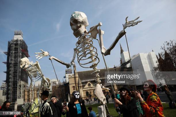 Environmental campaigners hold up a skeleton puppet as they take part in a coordinated protest by the Extinction Rebellion group on April 15 2019 in...