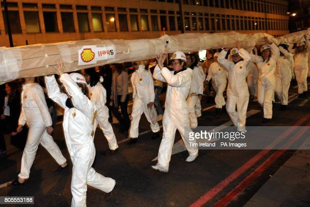 Environmental campaigners organised by Amnesty International carry a tube through Hoxton to protest against the activities of oil giant Shell in the...