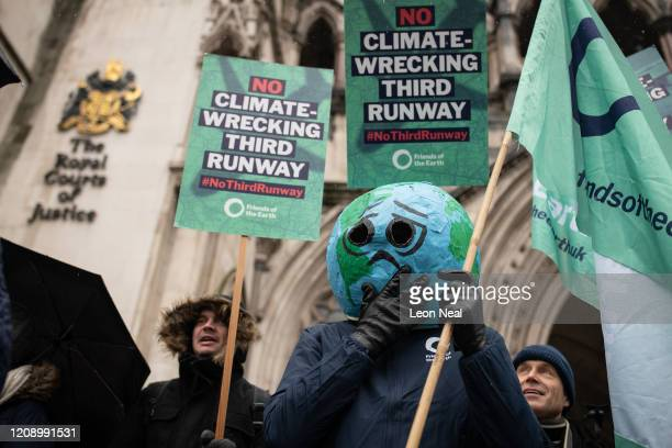 Environmental campaigners protest outside the Royal Courts of Justice ahead of the announcement of the ruling on the controversial third runway for...