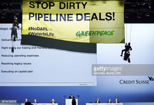 Environmental group Greenpeace activists hanging on ropes display a banner reading Credit Suisse Stop dirty pipeline deals as Credit Suisse CEO...