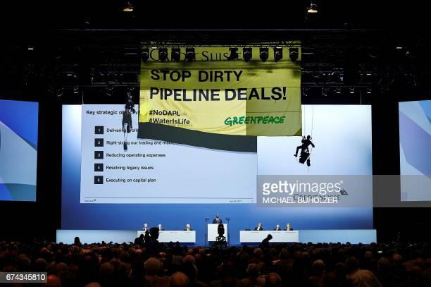 Environmental group Greenpeace activists hanging on ropes mount a banner reading 'Credit Suisse Stop dirty pipeline deals' as Credit Suisse CEO...