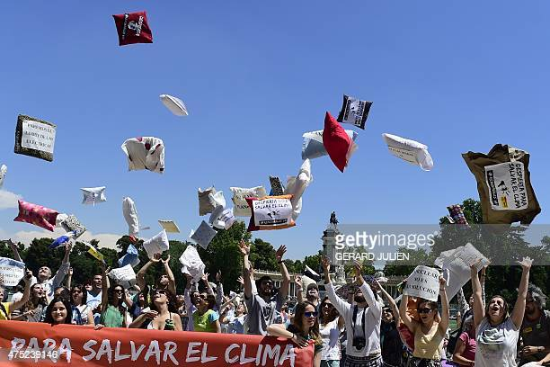 Environmental group Greenpeace activists throw pillows in the air beside a banner reading 'to save the climate' during an action dubbed ' Wakeup for...