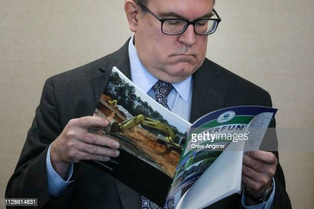 Environmental Protection Agency Administrator Andrew Wheeler looks at a pamphlet about Superfund sites before speaking at a press conference to...