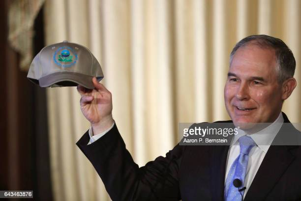 Environmental Protection Agency Administrator Scott Pruitt holds up an an agency baseball hat as he addresses employees at the agency's headquarters...