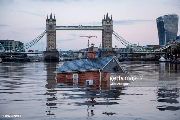 Environmental protest group Extinction rebellion float a replica of a British house infant of Tower Bridge on the River Thames in an action entitled...