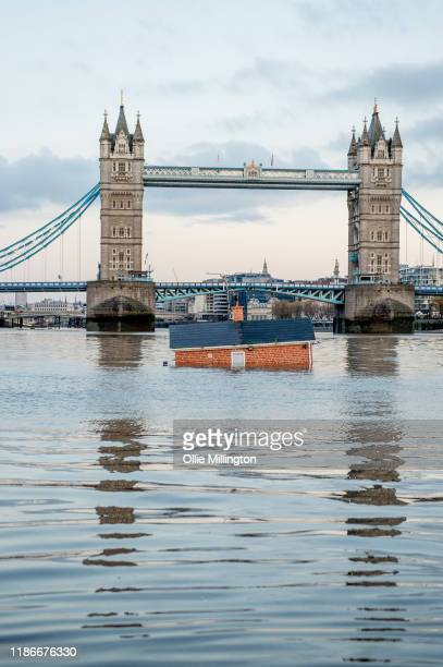 Environmental protest group Extinction rebellion float a replica of a British house infront of Tower Bridge on the river Thames in an action entitled...