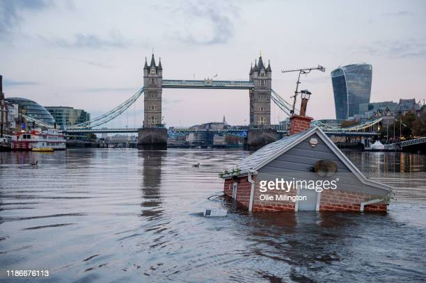 Environmental protest group Extinction Rebellion floats a replica of a British house in front of Tower Bridge on the river Thames in an action...