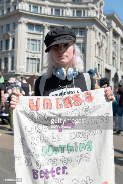Environmental protester is seen holding a small banner during the Extinction Rebellion Strike in London Environmental activists from Extinction...
