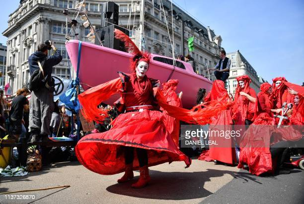 Environmental protesters from the Extinction Rebellion group in fancy dress dance in front of a pink boat at Oxford Circus as they take part in a...