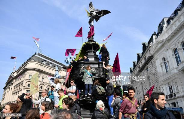 Environmental protesters from the Extinction Rebellion group waves flags as they stand on the Shaftesbury Memorial Fountain during a demonstration at...
