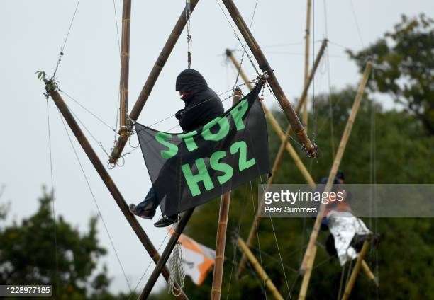 Environmental protesters hang from bamboo structures during a protest calling for an end to the removal of ancient woodlands along the proposed HS2...
