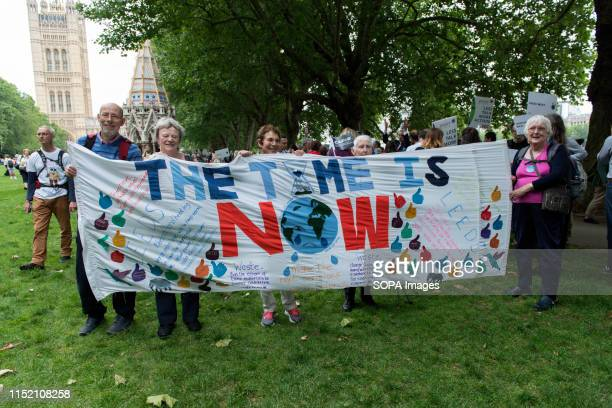 Environmental protesters hold a banner saying the Time Is Now during the demonstration Environmental protesters gathered around Westminster to lobby...