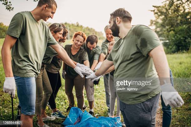 environmental volunteers giving group high five after successful cleaning nature from garbage - disability collection stock pictures, royalty-free photos & images