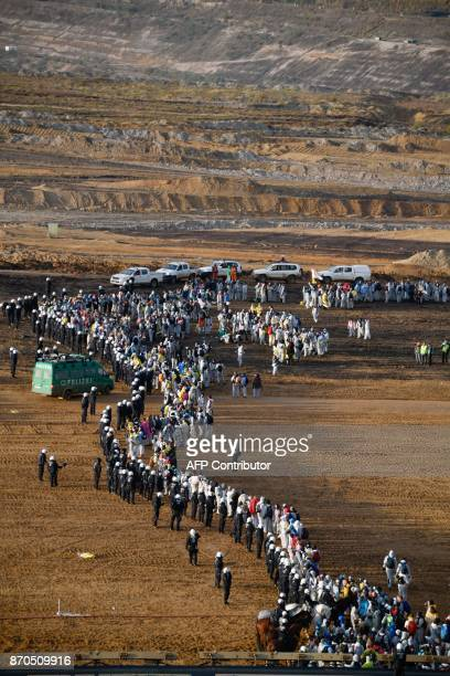 Environmentalist face policemen after they managed to enter the Hambach lignite open pit mine near Elsdorf western Germany on November 5 during a...