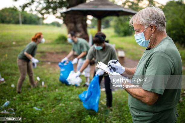 environmentalist keeping record of volunteer's work during environmental cleanup at public park - social responsibility stock pictures, royalty-free photos & images
