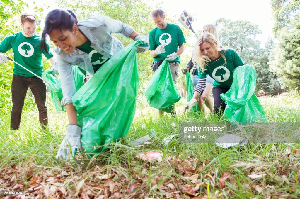 Environmentalist volunteers picking up trash in field : Stock Photo