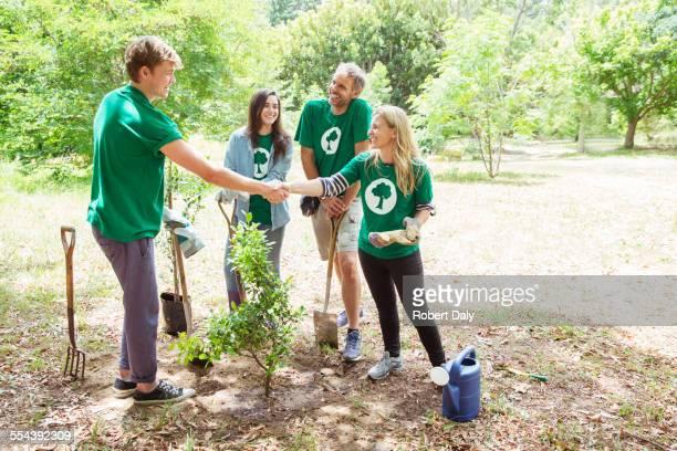 Environmentalist volunteers planting new tree and handshaking