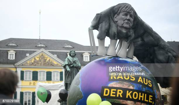 Environmentalists hold up an Earthshaped balloon reading 'Out of Coal' and decorated with an effigy of German Chancellor Angela Merkel seen in the...