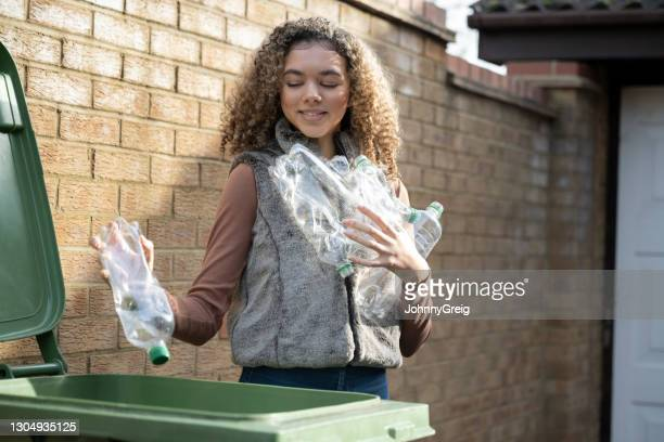 environmentally aware teenage girl recycling plastic bottles - mid length hair stock pictures, royalty-free photos & images