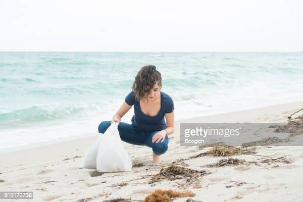 environmentally conscious millennial woman cleans up beach miami florida - riva dell'acqua foto e immagini stock