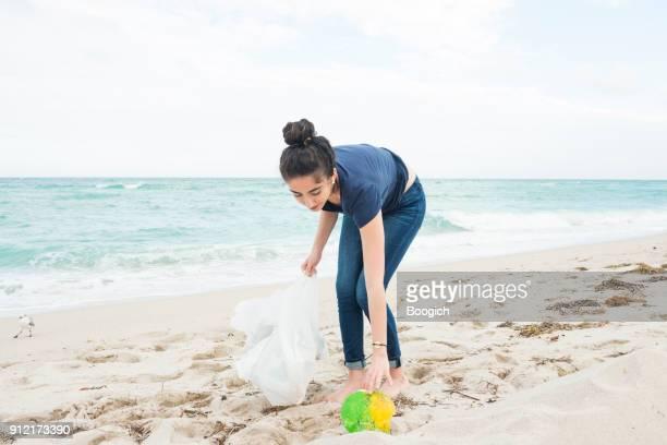 Environmentally Conscious Millennial Woman Cleans Up Beach Miami Florida