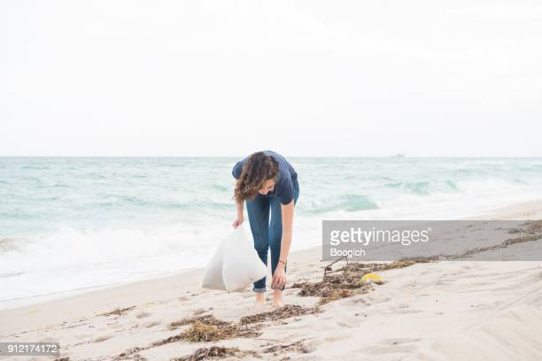 environmentally conscious millennial woman cleans up beach miami florida - sollevare foto e immagini stock