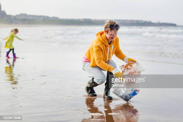 environmentally conscious woman cleans up beach - plastic pollution stock pictures, royalty-free photos & images