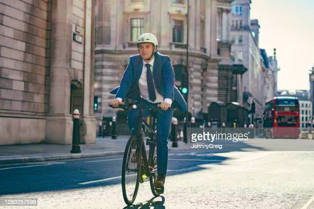 environmentally mindful british businessman cycling to work - bicycle stock pictures, royalty-free photos & images