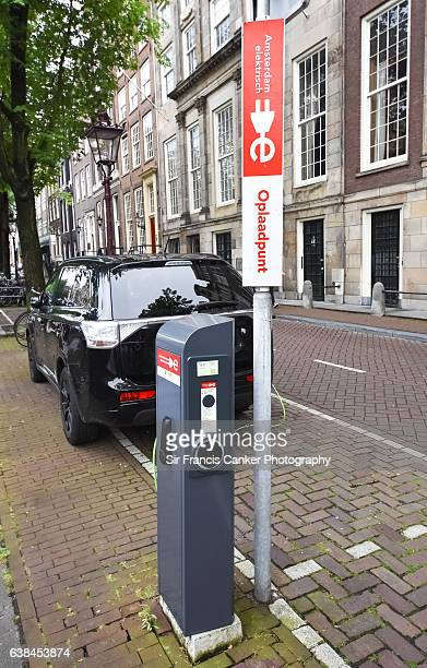 environmentally-friendly car charging station in old town of amsterdam, netherlands - electric vehicle charging station stock photos and pictures