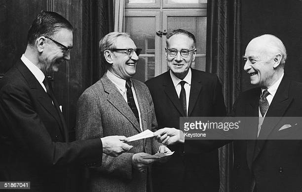 Envoy Nils Stahle hands over the cheques to the joint winners of the 1970 Nobel Prize in Medicine in Sweden 11th December 1970 From left to right the...