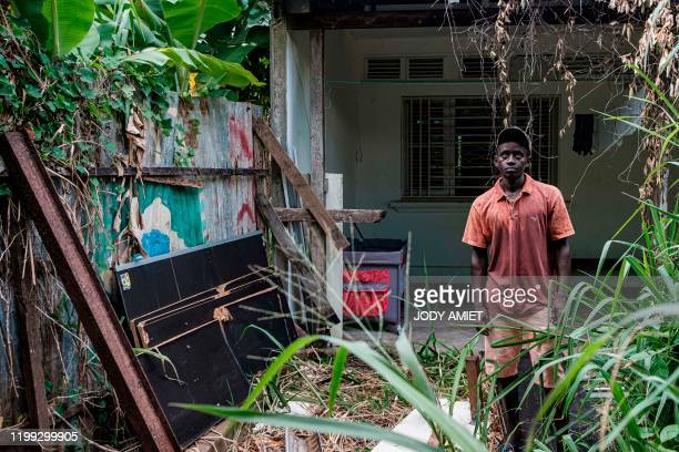 Enza 28 years old from Guinea Bissau poses in an abandoned house in Cayenne on February 6 after being evicted from a makeshift shelter in the Matine...