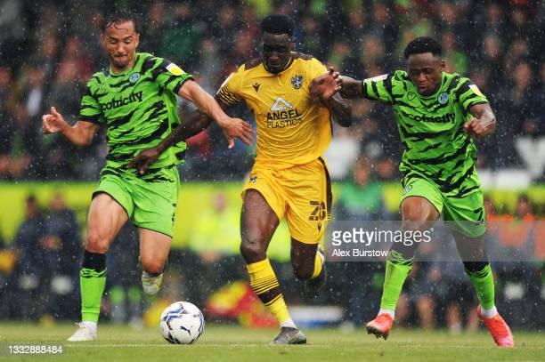 Enzio Boldewijn of Sutton United battles for possession with Kane Wilson and Udoka Godwin-Malife of Forest Green Rovers during the Sky Bet League Two...